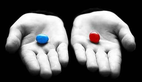 Foto em preto e branco de duas palmas de mão, cada uma contanto uma pílula, uma azul e outra vermelho.
