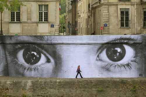 Foto mostra um muro que tem como imagem dois olhos e à frente dele uma pessoa andando
