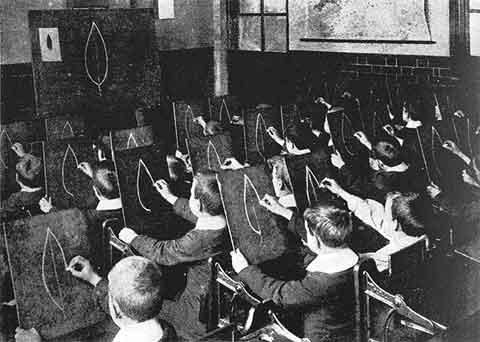 Foto em preto e branco de uma turma de crianças numa aula de desenho que copiam a mesma imagem do quadro em suas telas.