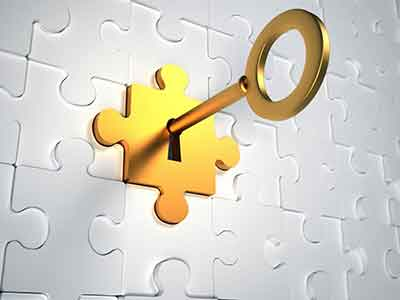 Chave de ouro encaixada numa peça de quebra cabeças também dourada que completa o painel de quebra cabeças.