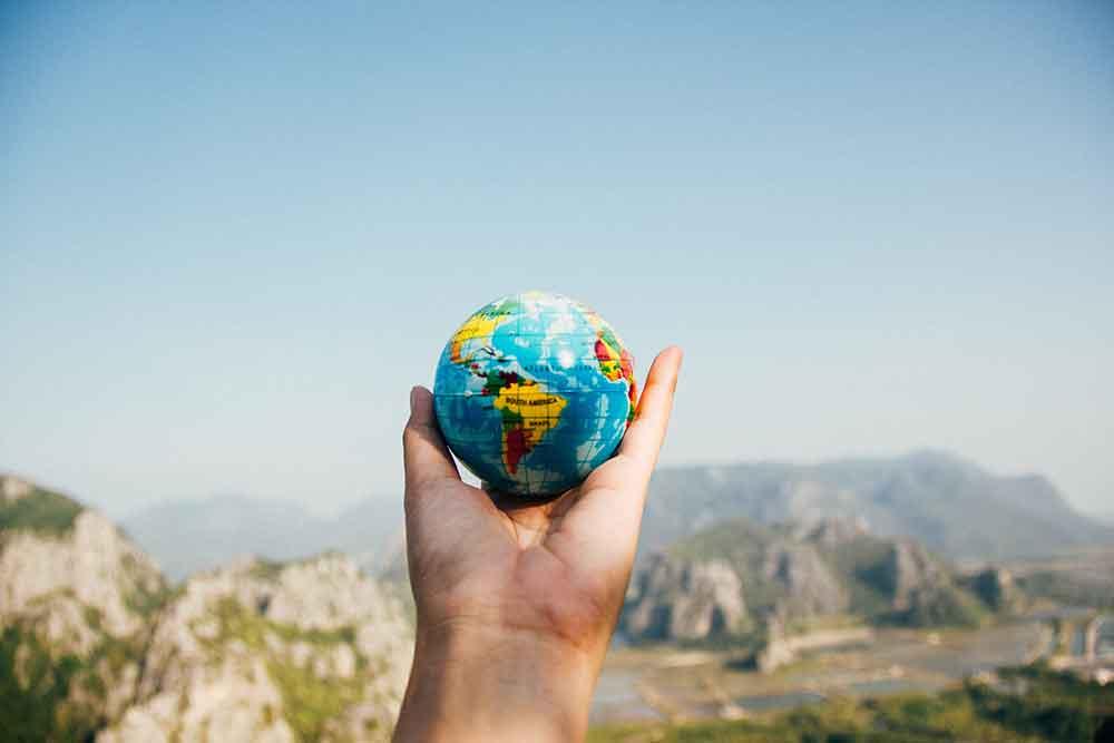 mão segurando uma bola do planeta Terra.